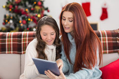 Festive mother and daughter using tablet on the couch Royalty Free Stock Photos