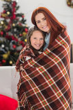 Festive mother and daughter wrapped in blanket Stock Photos