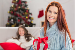 Festive mother holding a gift Royalty Free Stock Photography