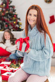 Festive mother holding a gift Stock Photography