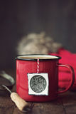 Festive mug of tea. Enamel mug with festive tea bag tag stock photography