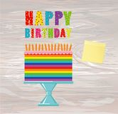 A festive multicolored and iridescent big cake with candles on a. Stand.  Empty Yellow sheet of paper for notes. Sticker. Happy Birthday. Greeting card or Stock Photo