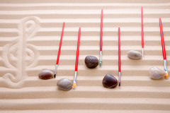 Festive music at the beach. Background concept with notes of waterworn pebbles and red paintbrushes overlying a score of alternating rows of colored sand with a stock image