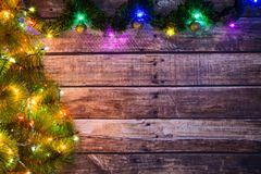 Festive New Year or Christmas background of dark old wooden boards, Christmas tree and luminous garland with colored lights and Ch. Ristmas balls for a banner royalty free stock photo