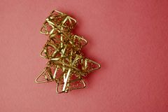 Festive New Year Christmas happy pink and blue joyful background with a small toy metal iron golden homemade Christmas tree. royalty free stock photo