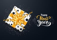 Festive New Year Greeting Card. New Year festive luxury design with square gift box and gorgeous golden bow on black background. Calligraphy inscription Happy Royalty Free Stock Photos