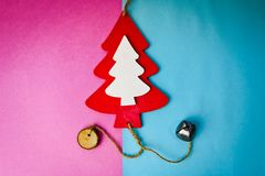 Festive New Year`s Christmas multi-colored joyful blue pink background with a small toy wooden red and white cute Christmas tree. royalty free stock photography