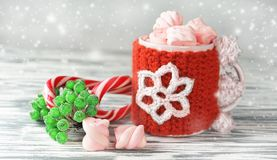 A festive New Year`s cup with hot coffee and marshmallow. A festive New Year`s cup with a knitted pattern in a cold winter evening with hot coffee or cocoa with Royalty Free Stock Photo