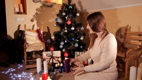 In the festive New Year`s environment near the Christmas tree, a girl blows out a purple candle.  stock footage