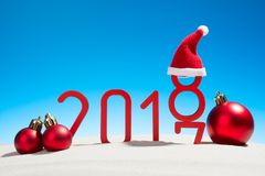 Festive New Years concept with Christmas balls a sunny tropical beach with the changing date 2017 - 2018 in red and copy space on. A blue sky i royalty free stock photos