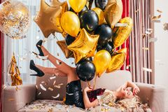 Festive occasion amused blonde girl balloons. Festive occasion. Amused blonde girl lying with balloons on sofa in festive outfit, high heels, legs up in air royalty free stock photo