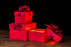 Festive opened boxes with bow and light on wooden background is Royalty Free Stock Photos