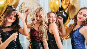Festive party amused dancing girls balloons. Girls festive party. Amused ladies in sequin cocktail dresses enjoying time together, having fun, dancing over royalty free stock images