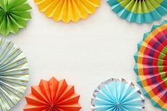 Festive and party background with colorful paper circle fans over wooden white background. Copy space. royalty free stock photography