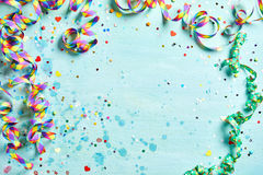 Festive party or carnival border. Of coiled streamers and confetti on a light blue green wood background with copy space stock images