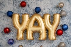 Festive patriotic USA American Christmas background featuring ornaments in red white and blue colors on blue marble background. YAY word in gold lettering stock image