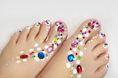 Festive pedicure . Festive pedicure with a design of multicolored rhinestones Stock Photos