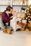 Festive photo of boy on chair and happy dad. On background of Christmas scenery Royalty Free Stock Photography