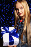 Festive photo of cute little girl with long blond hair holding a gift-box Royalty Free Stock Images