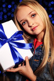 Festive photo of cute little girl with long blond hair holding a gift-box Stock Photography