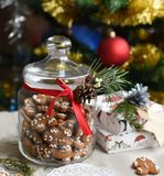 A glass jar of homemade gingerbread cookies, cinnamon sticks and other decoration elements against a backgrou. A festive photo with a glass jar of homemade Stock Image