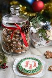 A glass jar of homemade gingerbread cookies, cinnamon sticks and other decoration elements against a backgrou. A festive photo with a glass jar of homemade Stock Photo