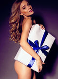 Festive photo of sexy blond woman holding a Christmas gift Royalty Free Stock Photos