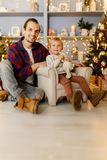Festive photo of son on armchair and happy dad. On background of Christmas decorations Stock Photography