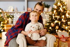 Festive picture of the father embracing his son sitting on chair. In background of Christmas tree with garland in studio Royalty Free Stock Photography