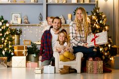 Festive picture of happy family against background. Of Christmas decorations, pine with burning garland in studio Royalty Free Stock Images
