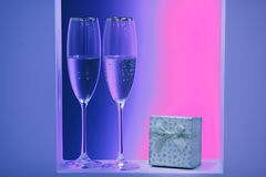 Neon pair of glasses of champagne in the holidays interior stock photos