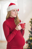 Festive pregnant woman holding mug while standing Royalty Free Stock Image