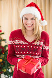 Festive pretty blonde woman offering gift Stock Photos