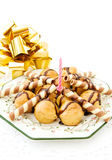 Festive profiteroles and golden ribbon. Celebrating a special day with delicious profiteroles and festive candle and golden ribbon. Isolated on white stock image
