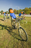 A festive pumpkin rides a bicycle along Crawford Notch, New Hampshire Stock Photography