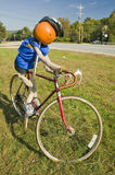 A festive pumpkin rides a bicycle along Crawford Notch, New Hampshire Stock Images