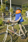 A festive pumpkin rides a bicycle along Crawford Notch, New Hampshire Royalty Free Stock Image