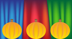 Festive Pumpkins. Three pumpkins in a row with a red, blue and green drapery background Stock Photography