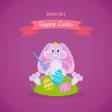 Festive rabbit is sitting on lawn and coloring Easter eggs. Happy easter greeting card. A nice festive rabbit is sitting on the lawn and coloring Easter eggs Royalty Free Stock Images