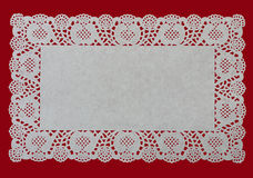 Festive rectangular cake doily, over red Royalty Free Stock Photo