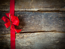 Festive red bow for a Christmas card. Festive red bow and ribbon forming a border for a Christmas card over rustic wooden planks with copyspace for your greeting stock photo