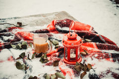 Festive red candle in lantern and mug of coffee on rug with snow Royalty Free Stock Photo