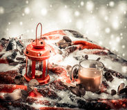 Festive red candle in lantern and mug of coffee on rug with snow Stock Photography