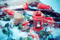 Festive red candle in lantern and mug of coffee on rug with snow Stock Photos