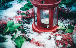 Festive red candle in lantern and mug of coffee on rug with snow Royalty Free Stock Photography