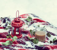 Festive red candle in lantern and mug of coffee on rug with snow Stock Images