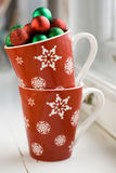 Festive red cup with snowflakes and balls on Christmas tree Stock Photo
