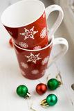 Festive red cup with snowflakes and balls on Christmas tree Stock Image