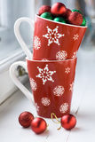 Festive red cup with snowflakes and balls on Christmas tree Stock Photography