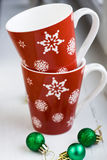 Festive red cup with snowflakes and balls on Christmas tree Stock Photos